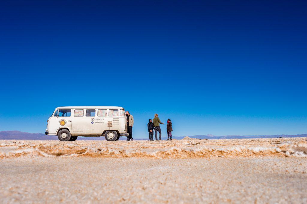 kombi e grupo de pessoas no deserto de sal na Argentina